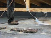 verkleben der Bitumenfolie auf dem Flachdach des Erweiterugsbaus