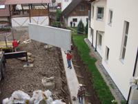 Eine Betonplatte wird mithilfe eines Krans an die richtige Stelle gehoben