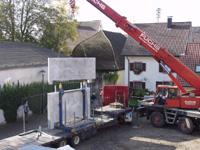 Ein Kran hebt eine Betonplatte vom LKW