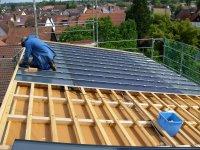 Mitarbeiter der Solarfirma installieren die Solarunterkonstruktionsplatten auf dem Pultdach