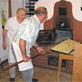 Bäcker schiebt Flammkuchen in den Steinofen
