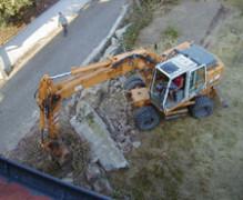 Bagger beim Einbrechen einer Steinmauer
