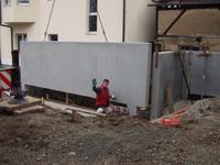 Ein Bauarbeiter weist das Absetzen einer Betonplatte an