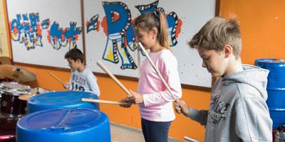 Drei Kinder trommeln auf Fässern
